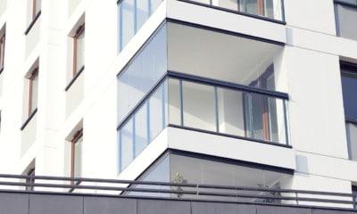Liten balkong helinnglasset med sømløse folde og skyveglass på toppen av glassrekkverk med mørke stolper